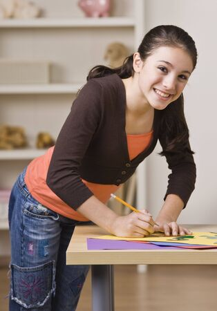 A young girl is working on a project and smiling at the camera.  Vertically framed shot. Stock Photo - 5333540