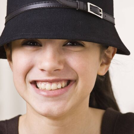 A young girl is wearing a hat and smiling at the camera.  Square composition.