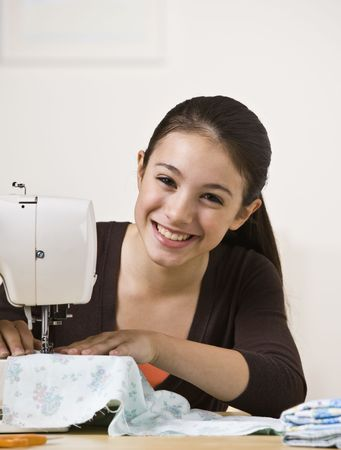 A beautiful young teenager sewing on a sewing machine.  She is smiling directly at the camera.  Vertically framed shot.