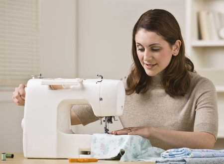An attractive brunette sewing in her home.  She has a slight smile on her face.  Horizontally framed shot.