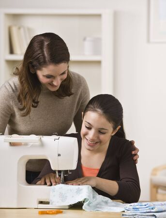 A beautiful teenage girl sewing on a sewing machine while her mother watches over her shoulder.  They are smiling.  Vertically framed shot. Stockfoto