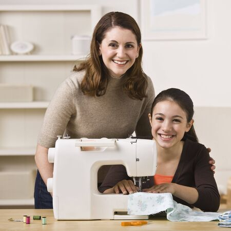A beautiful young girl sewing with her mother.  They are smiling at the camera.  Square framed shot. Stockfoto