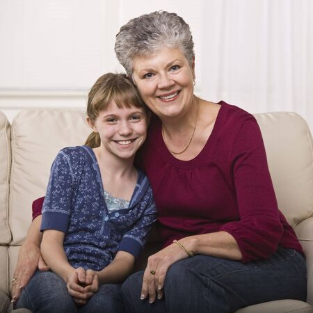 A grandmother is sitting on a couch and hugging her granddaughter.  They are smiling at the camera.  Square framed shot. photo