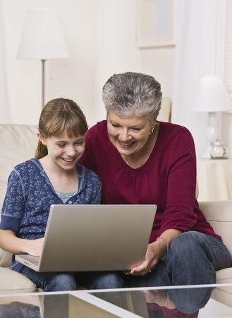 A grandmother and granddaughter use a laptop computer together at home.  Vertically framed shot. photo