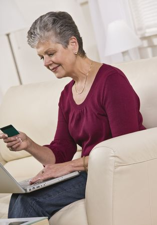 An elderly woman is seated in a couch with a laptop.  She is looking at a card in her hand and smiling.  Vertically framed shot. photo