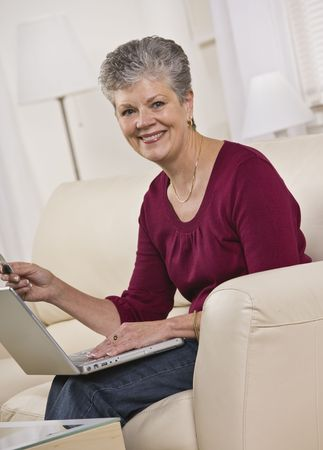 A woman is seated on a living room sofa and working on a laptop.  She is smiling at the camera.  Vertically framed shot. Stock Photo - 5334008
