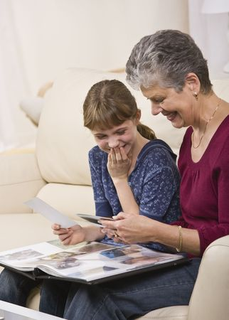A grandmother looking through a photo album with her granddaughter.  They are both smiling.  Vertically framed shot. photo