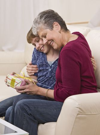 A grandmother hugs her granddaughter while holding a present. They are seated on a sofa and are smiling.  Vertically framed shot. photo