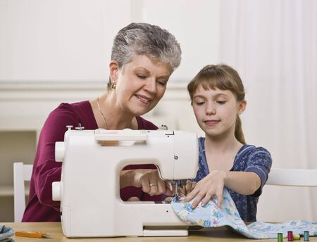 A grandmother and granddaughter using a sewing machine together. Horizontally framed shot. Stockfoto