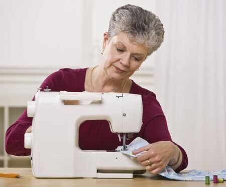 A senior woman sewing on a sewing machine in her home.  Horizontally framed shot. photo