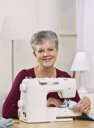 An elderly woman is working on a sewing machine in her home and smiling at the camera.  Vertically framed shot. photo