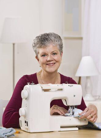 machine a coudre: Une femme �g�e travaille sur une machine � coudre chez elle et souriant � la cam�ra. Verticalement framed shot.