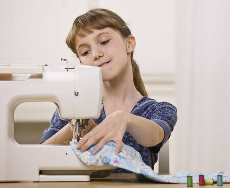to sew: A young girl is sewing on a sewing machine.  She is looking away from the camera.  Horizontally framed shot. Stock Photo