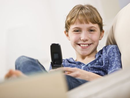 A young girl is holding a cellphone and smiling at the camera.  Horizontally framed shot. Stock Photo - 5333263