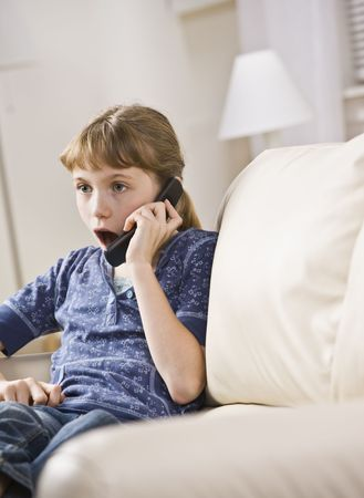 A young girl is seated on a living room sofa and is talking on a cellphone.  She is looking away from the camera.  Vertically framed shot. photo
