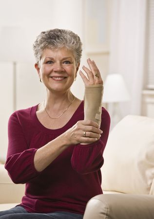 An elderly woman is putting a brace onto her hand and smiling at the camera.  Vertically framed shot.