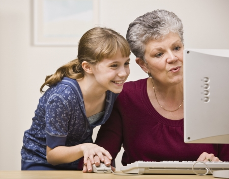 use computer: A senior woman and a young girl share a mouse as they use a computer together. Stock Photo
