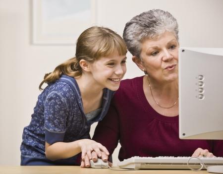 grandmother children: Una mujer mayor y una cuota de un rat�n joven, ya que utilizan un ordenador juntos.