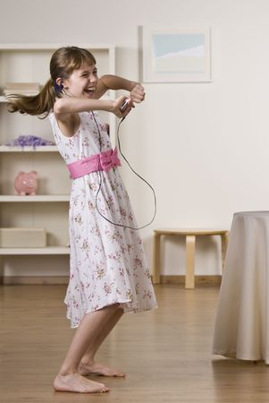 A happy little girl dancing to music.  She is listening to headphones from an Mp3 player.  Vertically framed shot. photo
