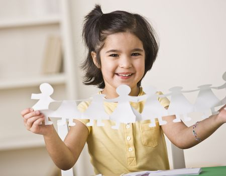 horizontally: A young girl is seated at a desk and is holding up paper dolls.  She is smiling at the camera.  Horizontally framed shot.