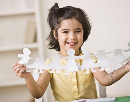 Een jong meisje zit aan een bureau en houdt updocument poppen. Ze lacht op de camera. Horizontaal framed shot.