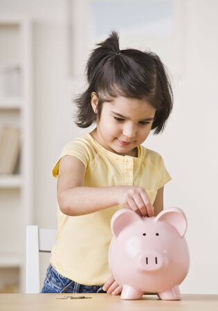 american children: A young girl is playing with a piggy bank.  She is looking away from the camera.  Vertically framed shot.