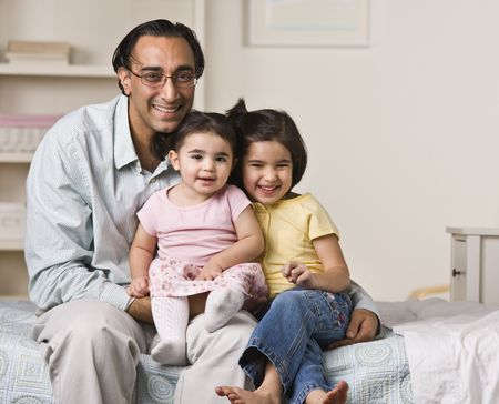 A father is sitting on a bed with his two young daughters.  They are smiling at the camera.  Horizontally framed shot. photo