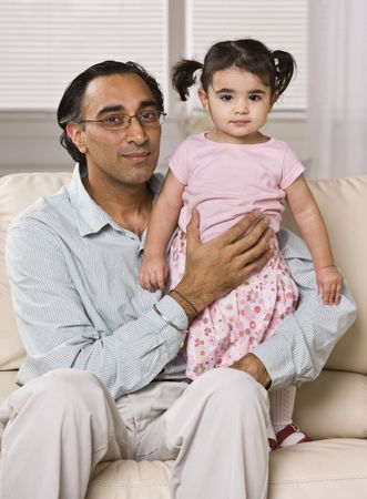A father is seated on a living room sofa and holding his daughter.  He is smiling at the camera.  Vertically framed shot. photo