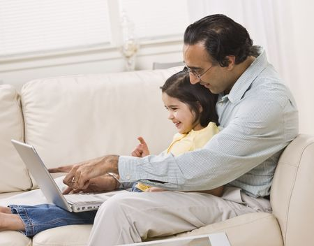 family sofa: A smiling Indian father and daughter relax on the couch together and share a laptop.  Horizontally framed shot.
