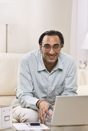 A man is seated in his living room and is working on a laptop.  He is smiling at the camera.  Vertically framed shot. Stock Photo - 5333668