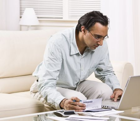 A man paying his bills online.  He has a checkbook in his hand.  Square framed shot. Stock Photo
