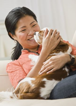 A woman is holding a dog in her arms, smiling, and looking away from the camera.  Vertically framed shot. Stock Photo