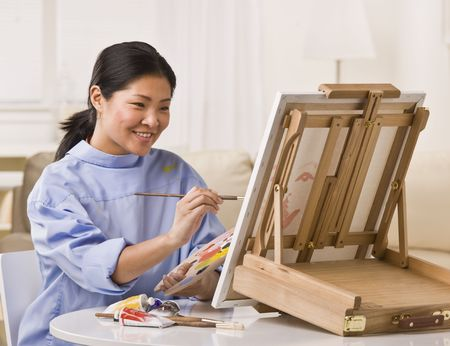 painting: Asian woman sitting at table, smiling and painting on small easel. Horizontal
