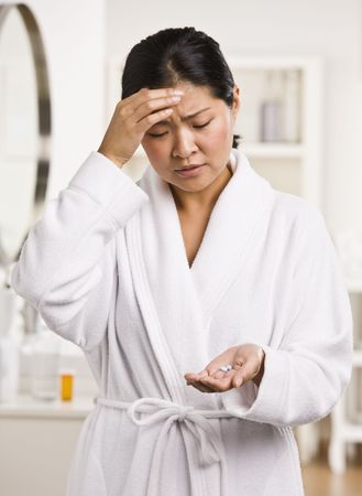 A young woman is holding pain medication that she is about to take for a headache.  She is looking away from the camera.  Vertically framed shot. photo