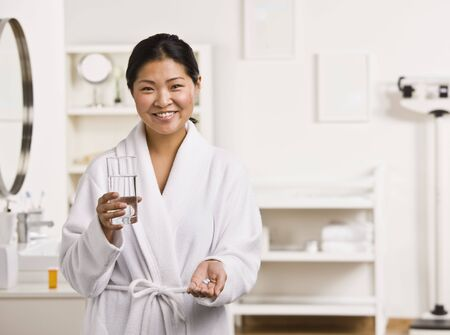 midlife: A woman is standing in a bathroom, and is about ot take some medication.  She is smiling at the camera.  Horizontally framed shot. Stock Photo