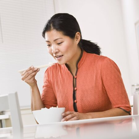 Asian woman eating a bowl of rice with chopsticks. Square photo