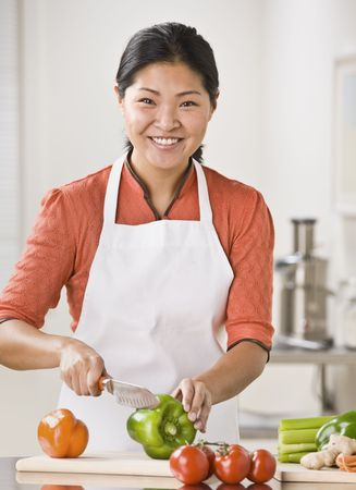 A woman is slicing produce in her kitchen.  She is smiling at the camera.  Vertically framed shot. Stock Photo