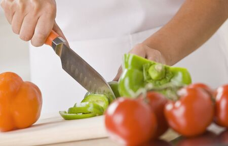 A woman is slicing produce in a kitchen.  Horizontally framed shot. Stock Photo