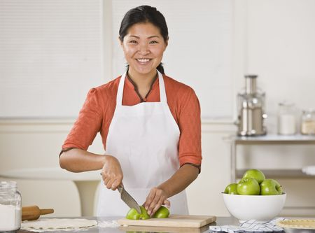Smiling Asian woman standing at counter and slicing apples.Horizontal