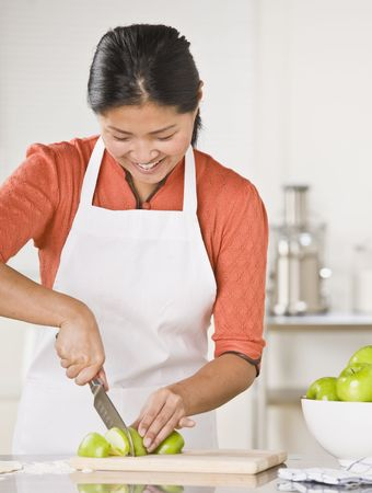 A woman is standing in a kitchen and slicing apples.  She is looking away from the camera.  Vertically framed shot. photo