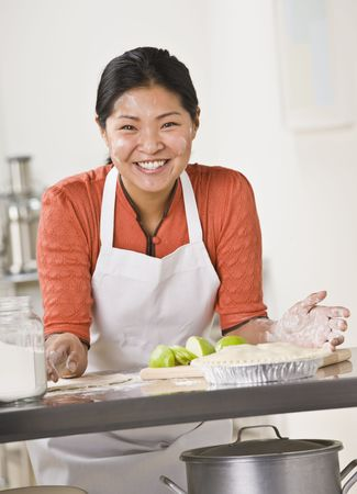 A woman is standing in a kitchen and slicing apples for a pie.  She is looking away from the camera.  Vertically framed shot. Stock Photo - 5333811