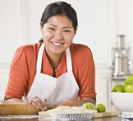 Asian woman rolling dough, making pie, smiling at camera with flour on her face. Square. photo