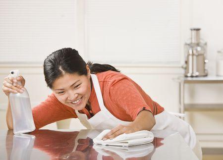huis opruimen: Een vrouw is het reinigen van het aanrecht. Ze kijkt weg van de camera. Horizont aal ingelijste schot.