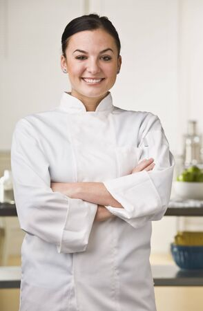 Attractive brunette, female chef smiling at the camera with her arms crossed. Vertical photo