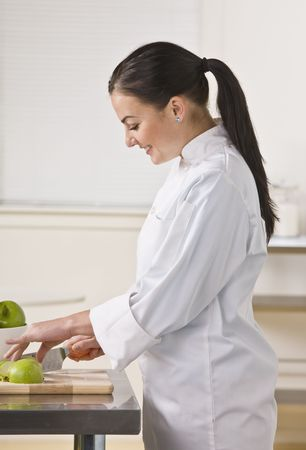 slicing: A woman is standing in a kitchen and slicing apples.  She is looking away from the camera.  Vertically framed shot.