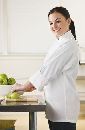 slicing: A young woman is slicing apples in a kitchen.  She is smiling at the camera.  Vertically framed shot. Stock Photo