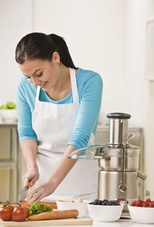 A woman is in her kitchen slicing produce.  She is smiling and looking away from the camera.  Vertically framed shot.