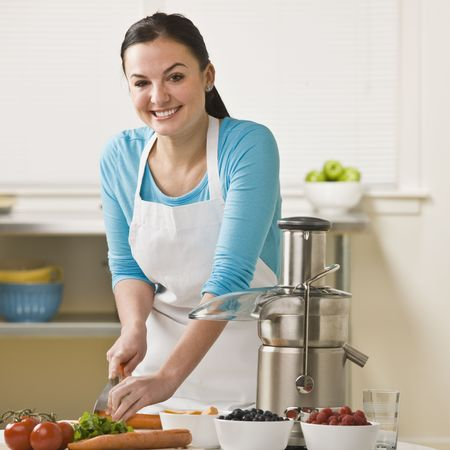A woman is in the kitchen and slicing produce for the juicer.  She is smiling at the camera.  Square framed shot. photo