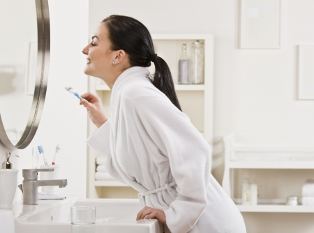 woman bathrobe: A young woman is standing in front of the bathroom mirror and brushing her teeth.  Horizontally framed shot. Stock Photo