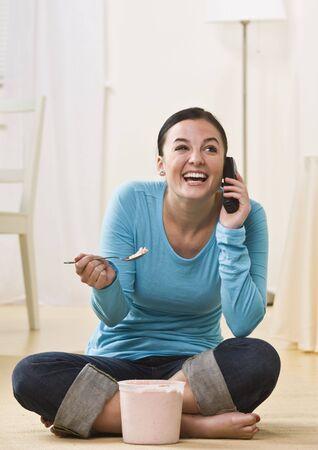 eating ice cream: Una joven est� hablando en un tel�fono y comer helado. Ella est� sonriendo y mirando a otro lado de la c�mara. Tiro vertical enmarcada. Foto de archivo